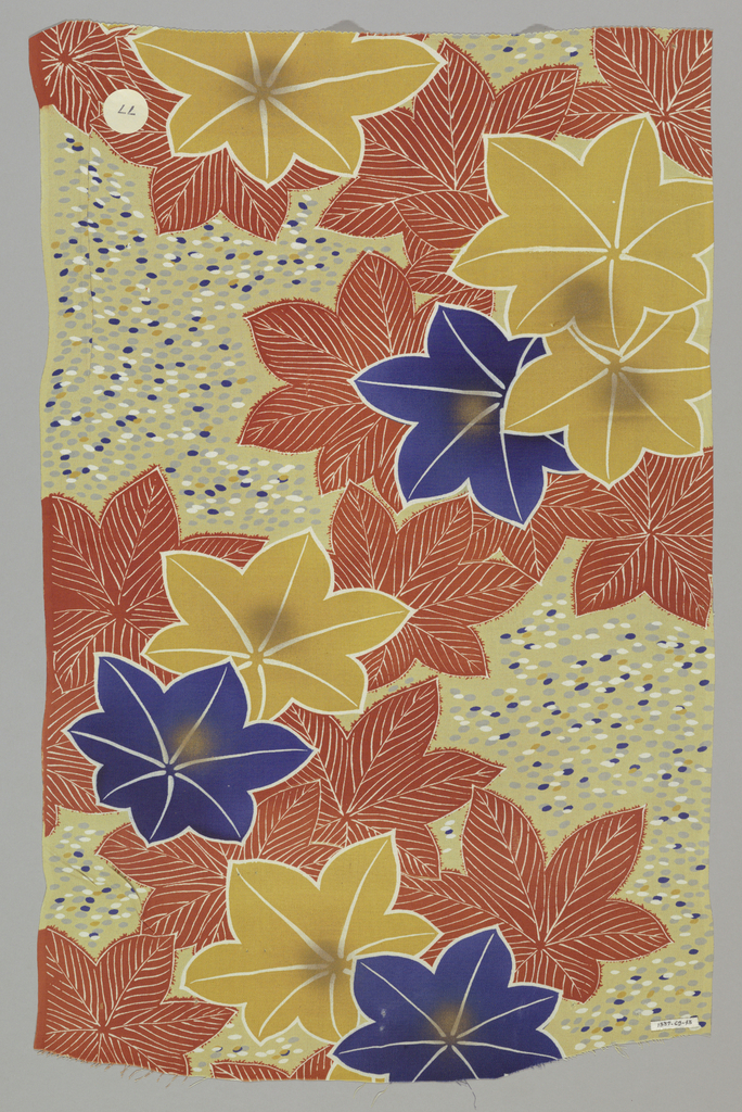 Pale yellow ground with dots of blue, grey, dark yellow and white has a design of large overlapping flowers in dark blue, dark red and dark yellow.