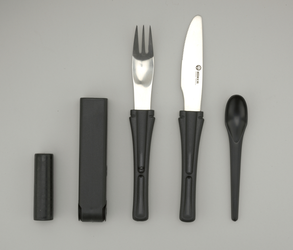 """Cutlery set consisting of tubular molded black plastic case (a), rectangular in section; small, recessed, salt and pepper shakers at curved end, having removeable circular lids with snap closures, molded with """"S"""" and """"P."""" Stainless fork (b), knife (c), each with tapering black plastic handle; small black plastic spoon (d).  Spoon nestles between knife and fork; all slide into case, handles exposed."""