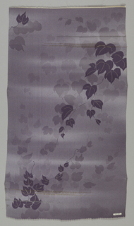 Ground with subtle shades of purple-gray with extra weft threads of gold and silver has a pattern of dark gray trailing vines. Vines printed in a lighter shade of gray fade into the background.