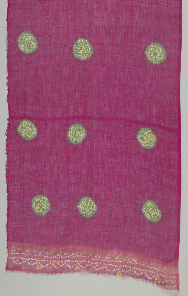 Length of bright cerise sheer cotton with widely placed green circular blotches with rosette inside in white and yellow dots. Vermillion ends with simple reserve pattern of dots in white, yellow, purple, green.