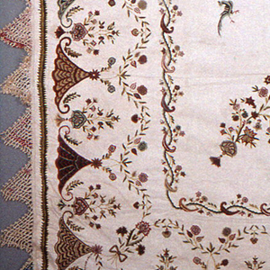 Design: Border on all four sides of fan-like shapes alternate with sprays of flowers. In the center a circle containing a figure holding a bow, wearing a sheath of arrows and carrying a spear. Embroidery losses in this area. Central circle is surrounded with a floral wreath. Floral sprays coming in diagonally from each corner. Isolated birds and floral sprigs on the field. Piece is surrounded with a woven fringe where the wefts have been braided into deep triangles. Colored silk has been tied to the crossings of the braids.