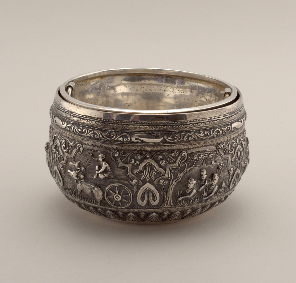 A). Hammered deep bowl, slightly contracting toward top. High repousse scenes of figures at various rural activities, encircled by strap-and-scroll work, and foliated bands.  B). A cylindrical inset with two hinged rings, and eight small holes in bottom. Stamped: The Gorham Co.