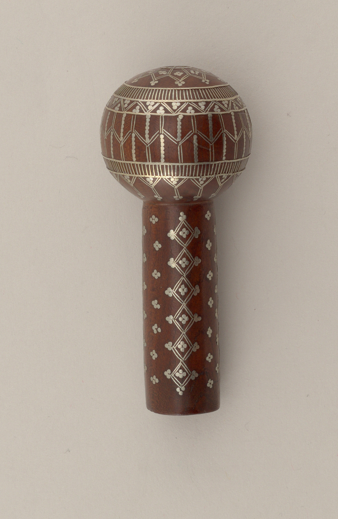 Round knob on short stem of wood, inlaid with silver. top has a star design; sides, stripes and zig-zags in circular bands; stem has perpendicular design of small conventionalized pattern and diamond in stripes.