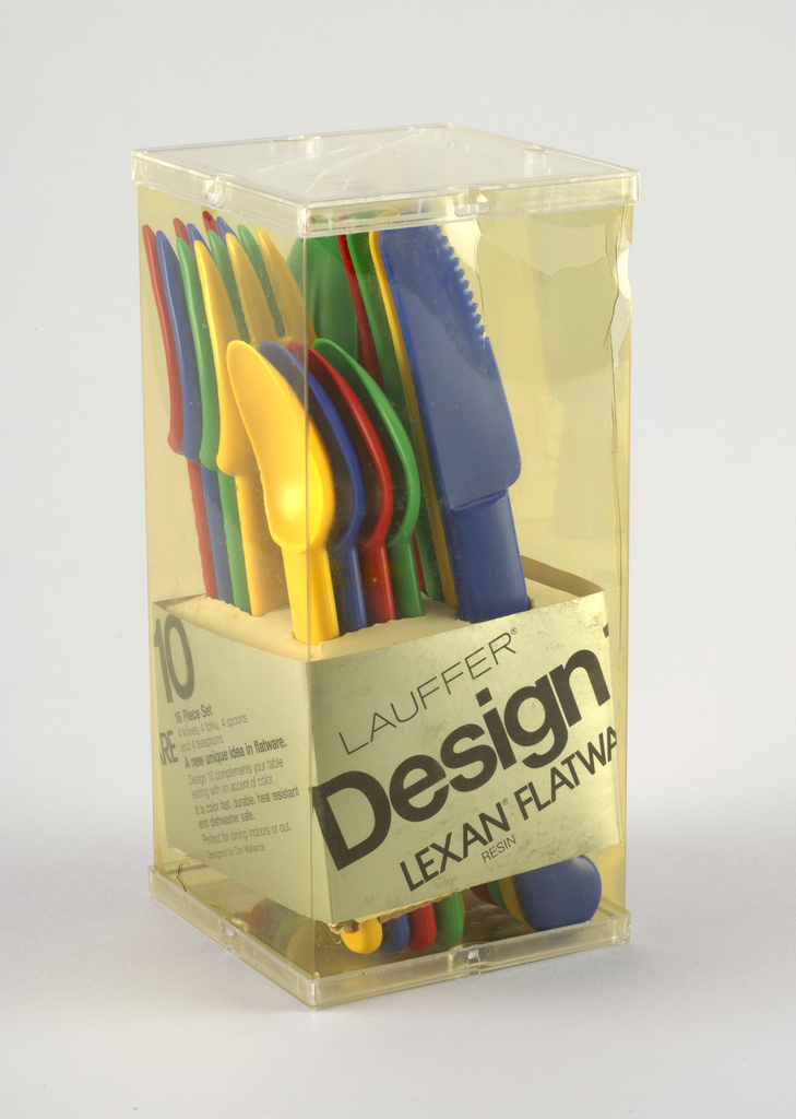 """Multi-colored plastic cutlery set (4 each of knives, forks, soup spoons and teaspoons in blue, red, yellow, green) housed in clear, upright rectangular box; cutlery held in place by cardboard insert at bottom of box. Paper label in box with """"Lauffer/Design 10/Lexan Flatware"""" printed on sides."""