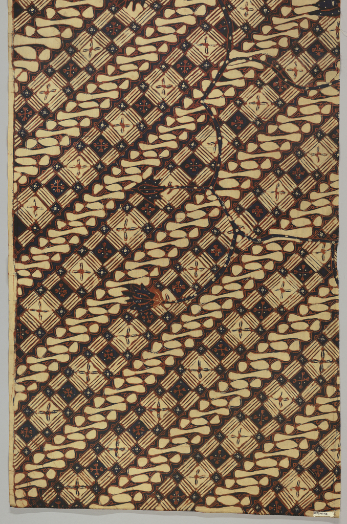 """One of two halves of a long narrow panel cut lengthwise. All-over pattern of two alternating diagonal bands: one made up of alternating dark and light squares and the other a series of curved scroll-like forms and dots (a version of the """"parang"""" or 'knife' motif). Serpentine floral branches are superimposed on the diagonal pattern. Dyed in deep indigo and rust-red."""