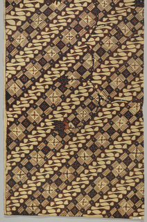 "One of two halves of a long narrow panel cut lengthwise. All-over pattern of two alternating diagonal bands: one made up of alternating dark and light squares and the other a series of curved scroll-like forms and dots (a version of the ""parang"" or 'knife' motif). Serpentine floral branches are superimposed on the diagonal pattern. Dyed in deep indigo and rust-red."