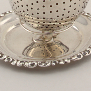 Orb-shaped infuser with chain; stand with wire work support on circular dish with scroll border.