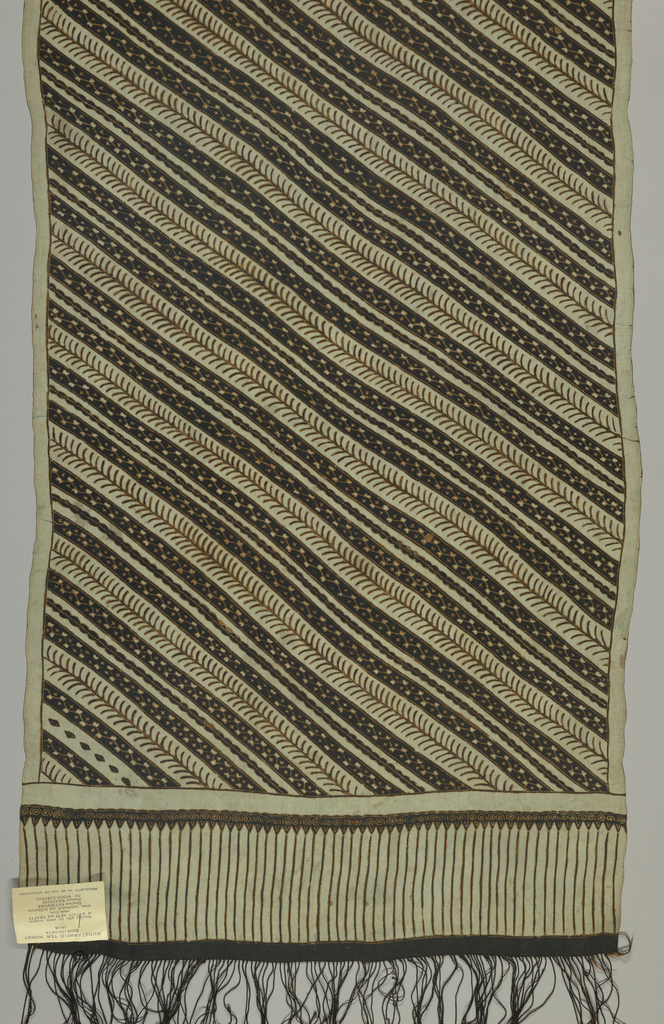 "Narrow shoulder cloth (selendang) in light green and dark brown showing an all-over pattern in diagonals (""garis miring"") of twigs and branches. Fringed."