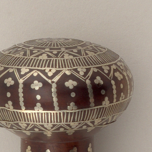 Small round knob, slightly flattened, set on short stem; wood inlaid in silver in completely conventionalized design; formed of small lines, dots in circular pattern or perpendicular pattern on stem.