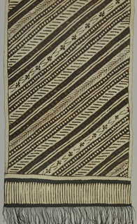 "Narrow shoulder cloth (selendang) in cream-white and dark brown showing design running in diagonals (""garis miring"") of small geometric shapes and twigs. Fringed."
