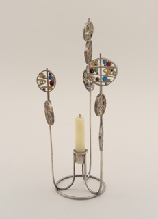 Candlestick with one central candleholder on a circular base surrounded by three towering stems, each with two or three circular forms filled with colorful enamelled abstract orbs contained within an angular grid of silver