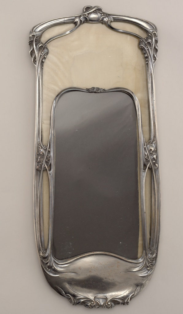 Vertical rectangular hanging frame with a rounded bottom.  Scrolled, entwined stems forming glazed tracery lined with a yellow-hued velvet; plate glass insert.