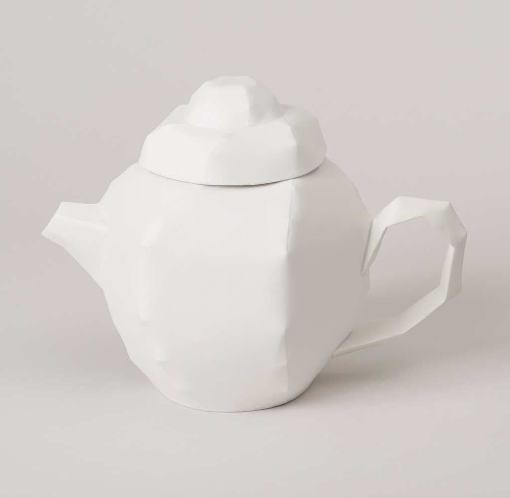 Matte white porcelain teapot (a) in hexagonal form with short spout, angular loop handle,and conforming lid (b) with domed finial; the form modelled to look like creased or folded and stitched paper, the appearance based on a paper prototype.