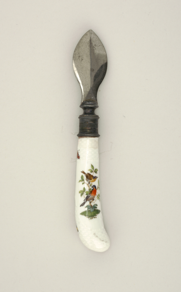 Spatulate point, bevelled on both sides.  The curved white handle decorated with small birds and insects in color, and moulded basketry texture at the ends.
