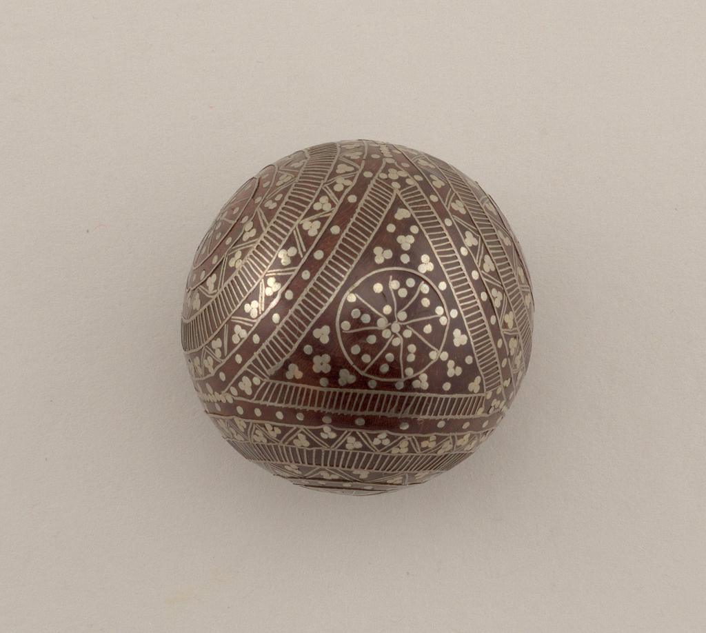 Round knob of wood inlaid with silver in designs of three circles, formed by bands of stripes, dots and conventionalized figures.