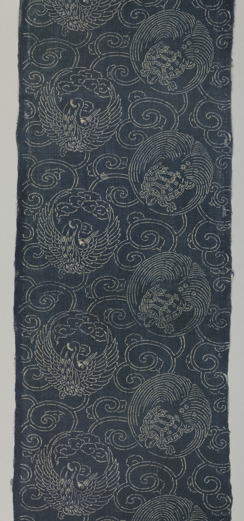 Design of turtles and cranes in white on dark blue.
