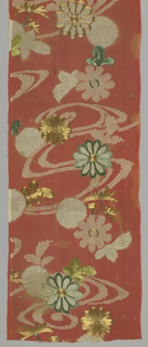 Kimono sleeve of red silk crepe – tie-dyed and embroidered in green silk and metallic thread. Pattern shows branches of chrysanthemums and leaves against red background.