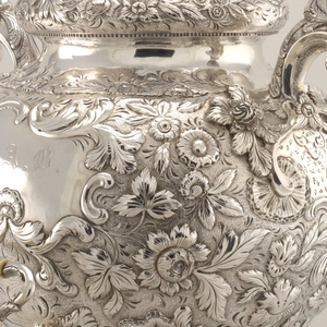 """Urn (b) consisting of bulbous circular section repoussé and chased with foliate scrolls and flowers on a punch work ground all centered by two rococo cartouches, the center engraved with initials """"J.A.B"""", the other on the back with initials """"J.B.P"""" on Gothic capital letters. Square base pierced with foliate scrolls. Lid (e) with matching floral and foliate decoration and rococo spiral knob finials, unmarked, granular base. Part of a repoussé and engraved tea set consisting of teapot (a), urn with lid (b,e), creamer (c), sugar bowl (d)."""