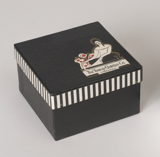 Small square carton covered with black paper with fine stippled all-over textural pattern. Rim of lid (b) has striped paper band affixed around edge. Die-cut paper label with logotype printed in black, red and metalic gold on light colored ground, affixed to lower right corner of box lid.