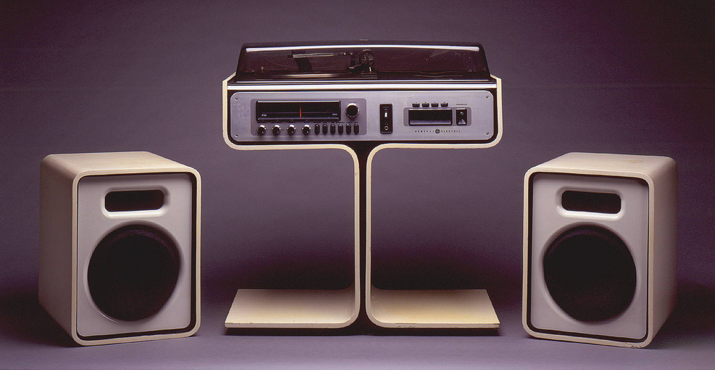 Unit comprising record turntable, radio/tuner and eight-track casette player in rectangular housing in top of white enameled wood pedestal (a); turntable and casette storage well in top, control knobs and radio on front; rectangular tinted plastic lid (b). Two upright rectangular speakers of white enameled wood faced with white plastic and dark fabric (c,d); speakers can fit on rectangular pedestal feet on either side of center column.