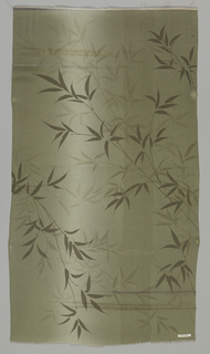 Shaded dark green-gray ground with some extra wefts of gold and silver has a pattern of bamboo branches in dark and light greenish tones.