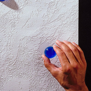 White, textured surface having the appearance of rough plaster. Has evenly spaced flat circular areas for the placement of blue glass beads, running diagonally up the sidewall.
