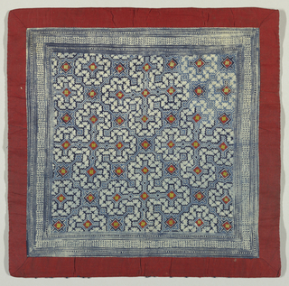 Part of a baby carrier or a head cloth (kain kepala) in cap (tjap) printed in geometrical motifs with little yellow floral shapes (possibly bits of silk cocoon) sewed onto red cotton diamonds. Wide border of red cloth sewn around the edges.