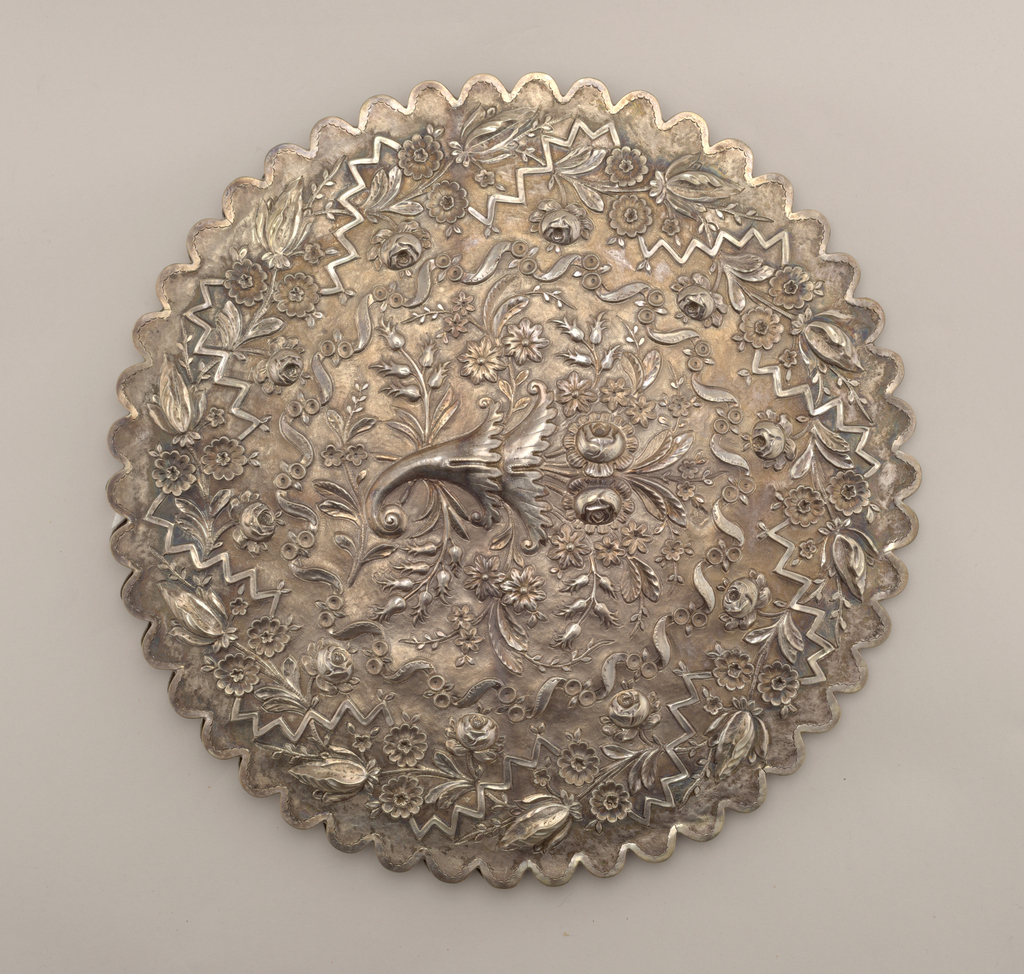 Scalloped circular silver frame engraced with leaves and flowers holding mirror glass. Back repousse with floral wreath, with horn-of-plenty bouquet in center.