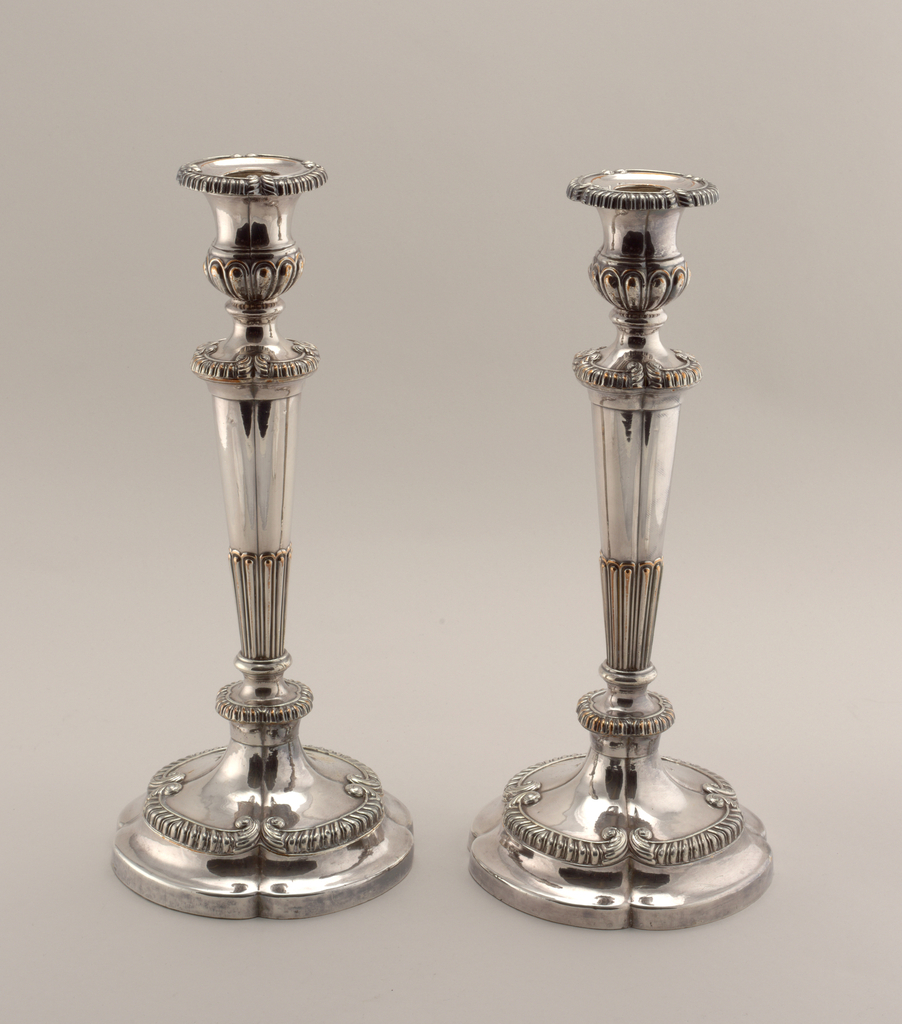 Four-lobed foot with gadrooned C-scrolls and collar. Four-lobed column, fluted in lower part, with gadrooned collar. Urn-shaped candle holder with gadrooned four-lobed rim. Weighted.