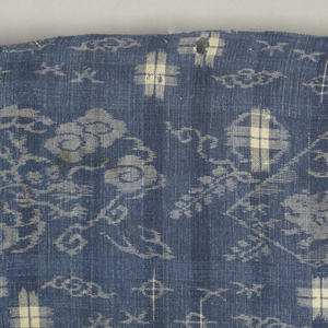 Medium-scale repeat of curling dragon in clouds alternating with prancing animal in diamond frame superimposed on a curving branch with flowers. Scattered plaid crosses in double ikat. In white reserved on blue ground.