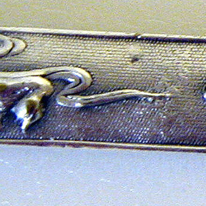 Knife in the form of a Japanese sword; handle with mottled surface, one side decorated with scene of a scholar (?) and guardian figure holding a large sword; other side depicts ducks. Flat, curved blade engraved with stylized foliate decoration.