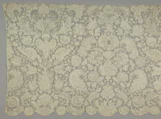 Point de France worked in a close, allover design of conventionalized flower and leaf forms on a ground of grandes brides picotées. Irregularly scalloped edge formed by the foliation.
