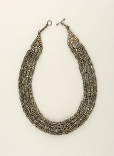Four strands of links of graduated length, alternately beaded and fasetted, on concealed inner chain; fastened at ends to two triangular elements decorated with filigree and flattened granules; ring and bolt closure.