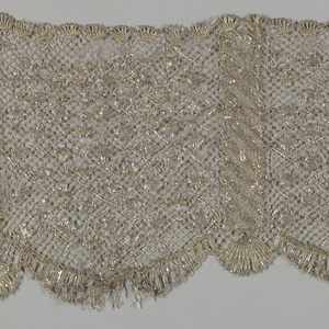 Wide border of metallic silver lace in all-over small scale repeated diamond shape, divided at intervals with a stripe. Outer edge is scalloped.
