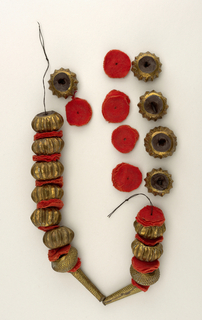 Necklace: Thin metal (copper or gilt alloy) with tooled ornaments, each bead filled with composition. Cloth disks separate the beads from each other. Most beads are roughly flattened spherical. Two adjoining are conical tubular.