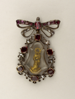 Bell-shaped pendant, surrounded by wreath of garnets and small rose diamonds, attached to bow-tie pin, again studded with garnets and diamonds. Pendant of thick glass contains an image in gold of Madonna and Child.