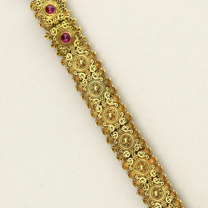 Gold beads, delicate patterns of filigree on upper surface, six mounted with cabochon rubies, and under surface of each bead consisting of angular gold elements, polygonal.
