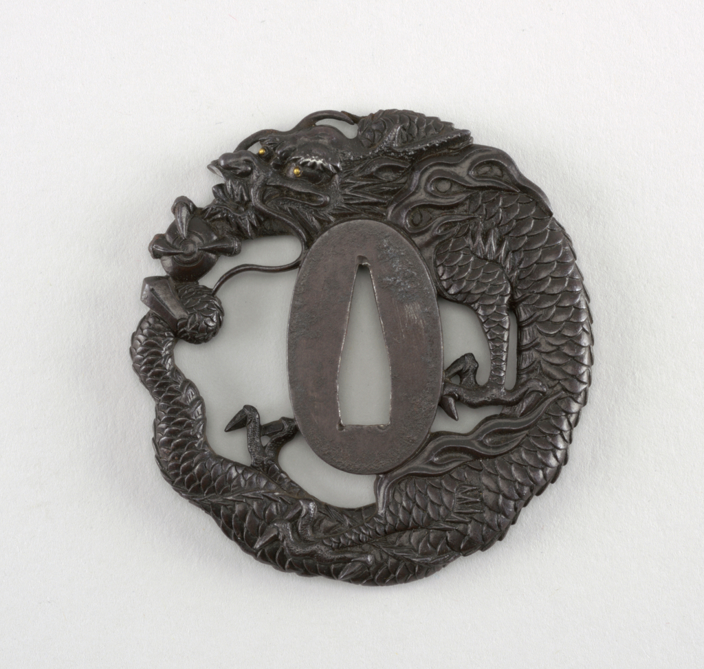This tetsu (iron) tsuba is naga maru gata (round) in shape. It has sukashi marubori (round openwork carving) in the form of a dragon and jewel. Surrounding the central nakago-ana, the opening through which the sword passes, is the seppadai, a flat oval area that is migaki (burnished).
