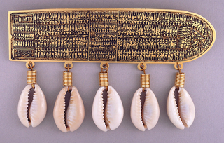 Modeled after diagram of a slave trade ship seen from above, showing the lower deck densely packed with a cargo of slaves; five cowrie shells hang from the lower edge.