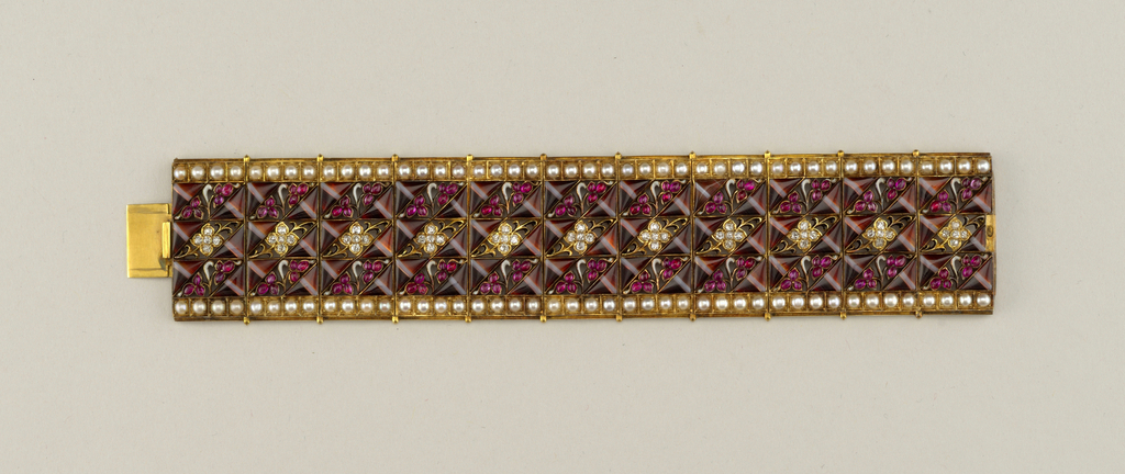 Wide gold and enamel bracelet with 100 cabochon rubies, 55 round diamonds, and 88 half pearls.