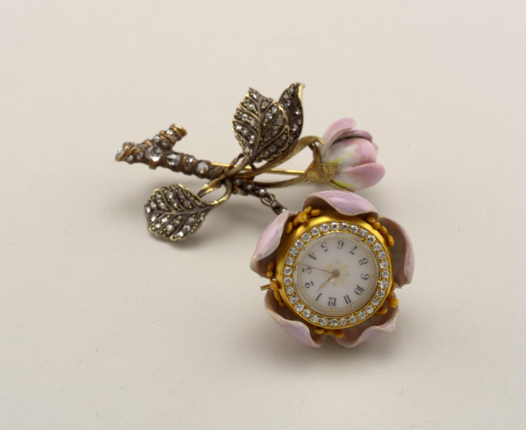 Chatelaine watch forms the core of a wild rose, the stem and foliage of which are composed of enameled gold, studded with diamonds. - Bar pin with three leaves, encrusted with small rose diamonds. - Branch set with large rose diamonds. - Pink enamel bud (few chips on edge). - Pendant watch, pink enamel hung from small rose diamond chain.  - Five pink enamel petals, old mine diamond clusters on base of watch, containing approximately 1 ct.. Cluster of old mine diamonds on border of face.  (This lapel watch was shown at the 1889 Universal Exposition in Paris, where TIffany exhibited a group of floral brooches.)