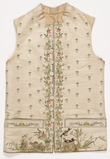 Gentleman's waistcoat of white satin with a small standing collar is cut straight across the bottom with straight pocket flaps and ten buttons. Embroidered in multicolored silks with a detached linear motif across the front. Flower border extends down the center front. Both pockets have a yellow butterfly. Under one pocket, two sheep worked in chenille thread, and the other side has two birds, one in a nest.