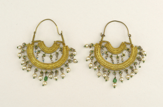 Pair of earrings of gilt metal, filigree, the outer half circle form has suspended white glass pearls and beads in green and turquoise.  Inner circle is set with pendants.