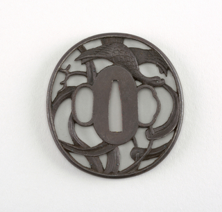 This iron tsuba is shinmaru gata (a true circle) in shape, and is crafted with sukashi (openwork) with a positive design showing Omodaka plants and a bird. At the center is a nakago-ana, an opening through which the sword passes. Surrounding this is the seppadai, a flat oval area that has a migaki ji (smooth) surface finish. On either side are ryo-hitsu, openings for the kozuka (utility knife) and the kogai (skewer tool). At right is sashi ura, the side which faces the blade, whose opening takes the negative form of a moon. Opposite is the sashi omote side, which faces the sword hilt. Its tri-lobed opening is of the suhama type, and symbolically represents the coastline of Horai, the holy island of the Immortals. The rim of the tsuba is round, or maru-mimi.