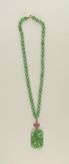 Necklace of 56 green jade beads, strung symmetrically with gold rings. Flat rectangular pendant carved with foliage, flowers, and buds. Attached to beads with gold wire and separated by an oval rose-quartz bead.