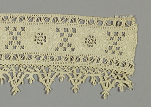 Border fragment with diamond-shaped areas filled in with needle lace. Tiny openwork squares are grouped in between diamond-shaped areas. Pointed lace border.