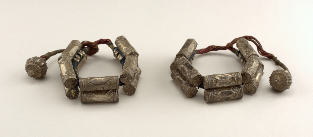 Pair of silver anklets. Five cartridge shapes, with decorative balls, on cord.