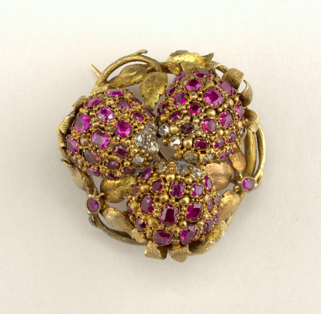 In the form of three berries, with gold leaves and stems.  Eleven diamonds, fifty-eight rubies.  One loose berry was repaired in 1957 (see object card for details).