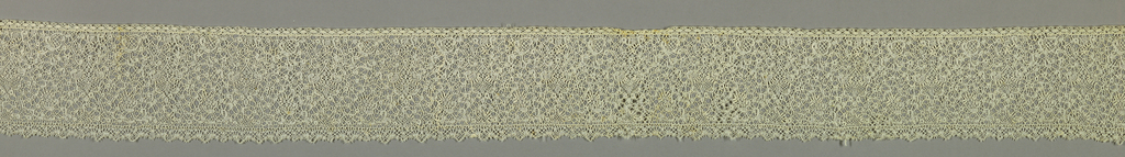 Binche style of scrolling ribbon like design with snowballs and braided connections.