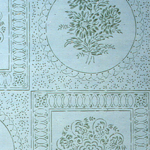 Stenciled tile pattern with floral sprigs in round medallion alternating with round stylized foliate design in square medallion. Printed in green on white ground.